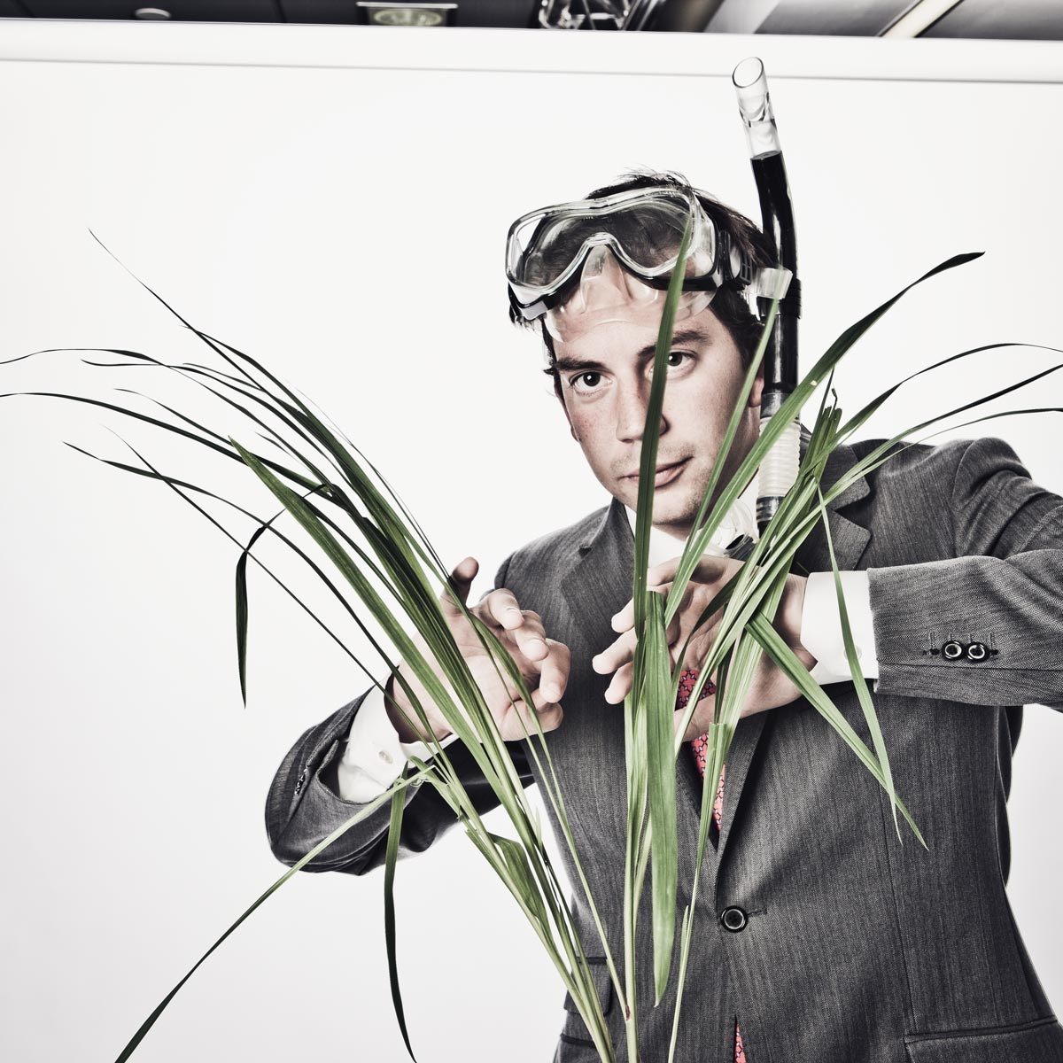 Businessman looking through grass