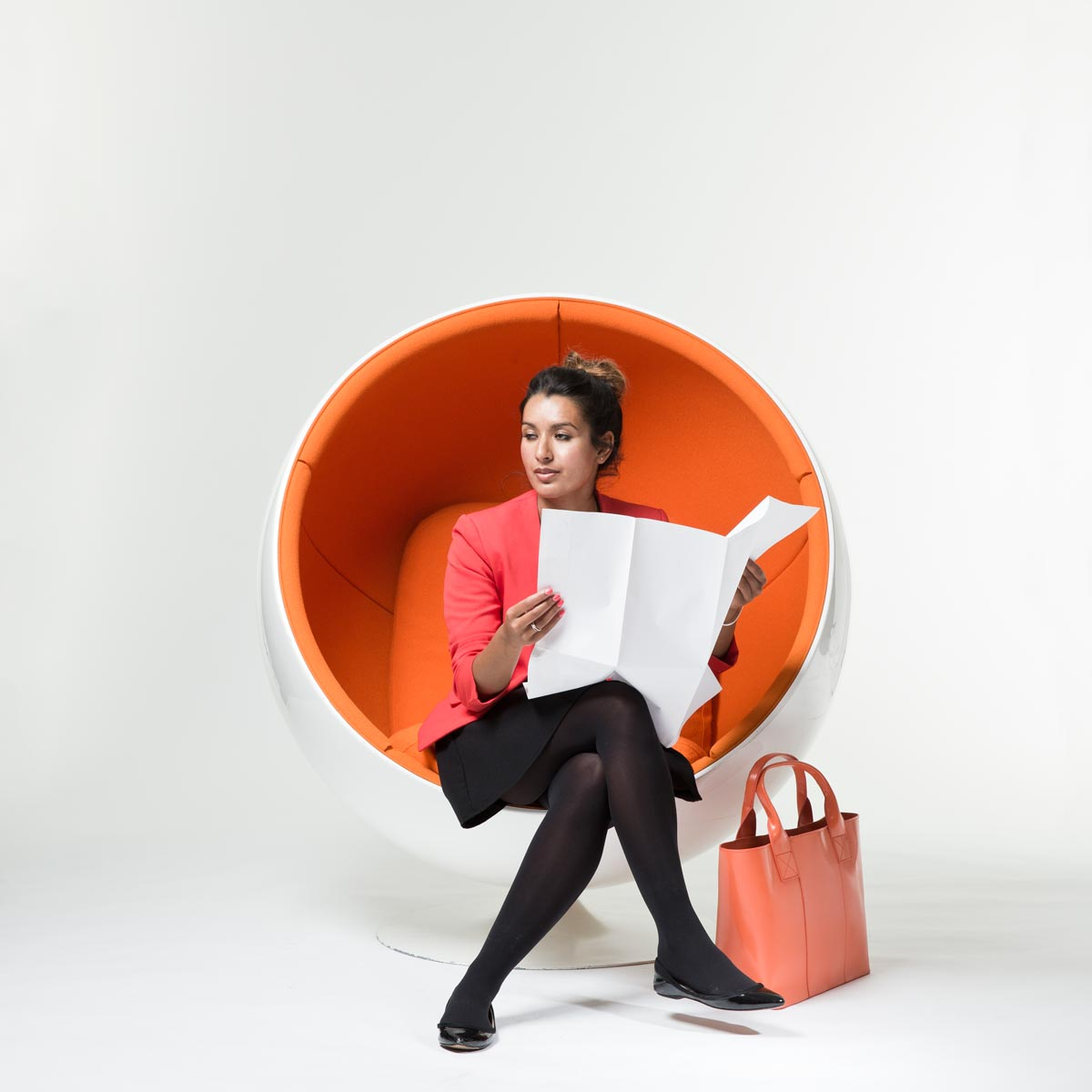 Woman reading paper in orange chair