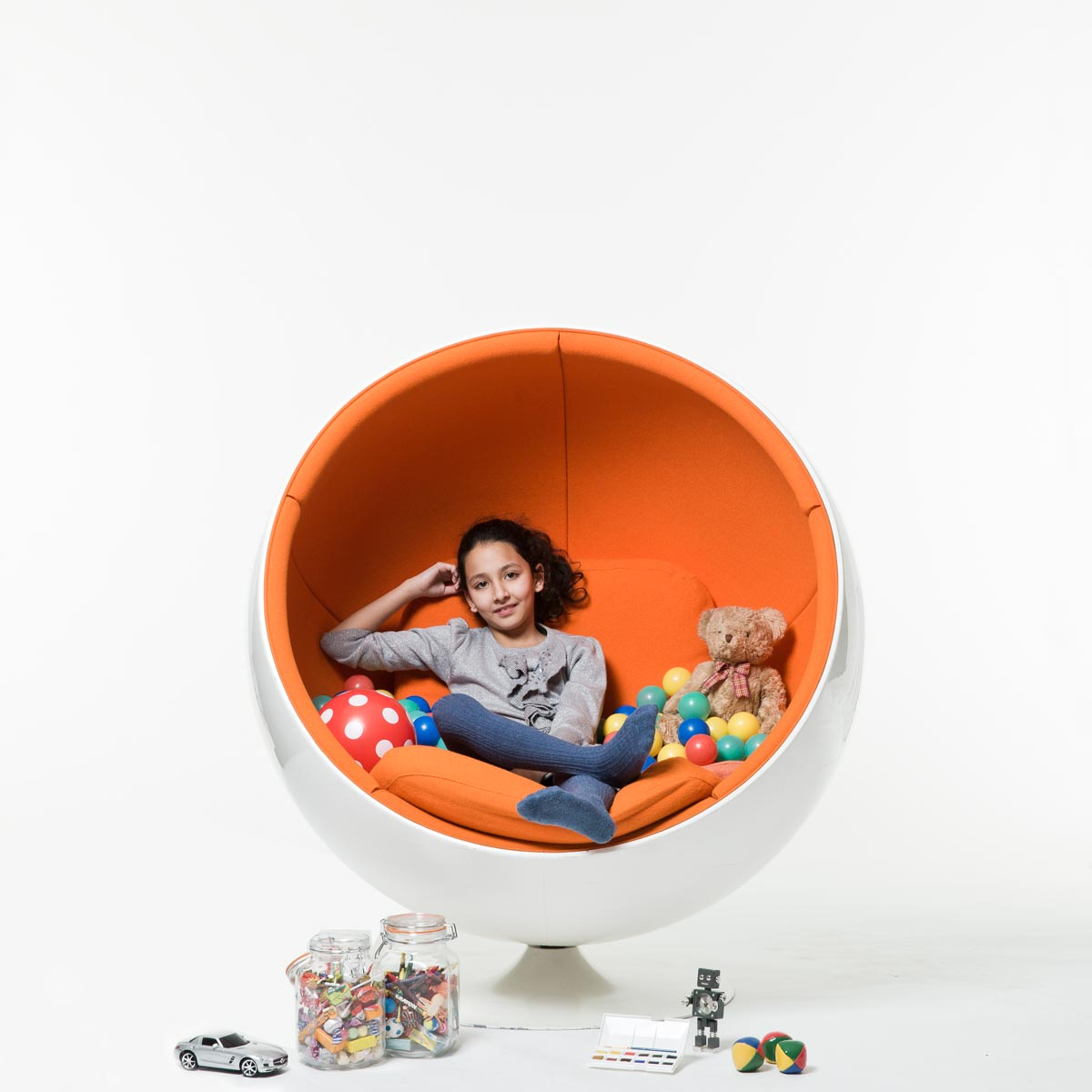 Young girl with toys sitting in orange chair