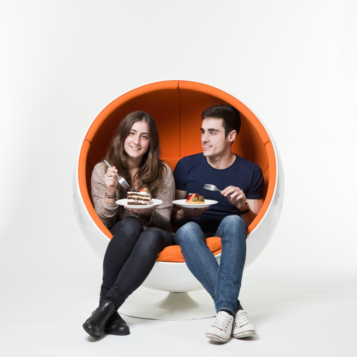 Two people sitting in orange chair